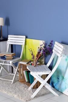 Дизайн комнаты с белой мебелью, книжный шкаф, фотографии цветов на синей стене
