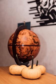 In the room a globe near the pumpkin