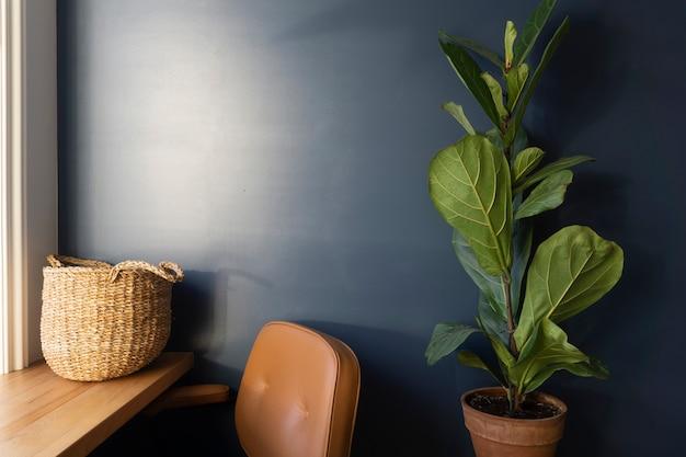 ワークデスクと青い壁のある室内。青い壁を背景に部屋の内部に緑の植物や花。