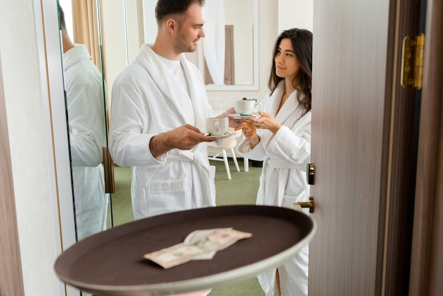 Room service delivering coffee to a hotel room for married couple wearing bathrobe who is giving dollar tips