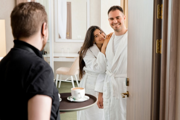 Room service delivering coffee to a hotel room for married couple wearing bathrobe