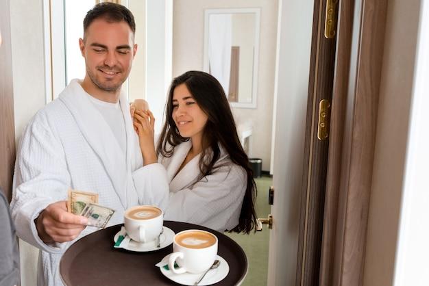 ドルのヒントを与えているバスローブを着ている夫婦のためにホテルの部屋にコーヒーを届けるルームサービス