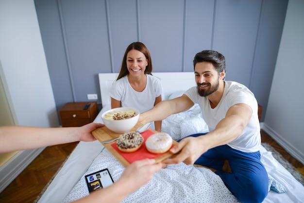 ルームサービス。ホテルの部屋で朝食を食べて幸せな若いカップル。幸せで恋に見えます。