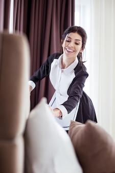 ルームサービス。彼女の仕事をしながら部屋を掃除するうれしそうなプロのホテルのメイド