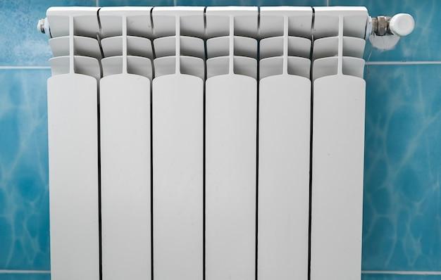 青い背景で暖房するための部屋の白いバッテリー。高品質の写真