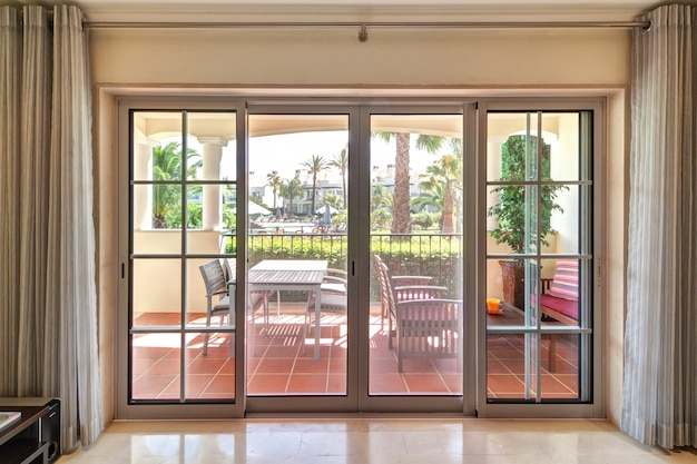 Окно комнаты с видом на террасу и зеленые сады.