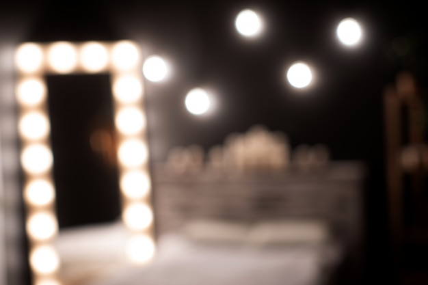 A room with a mirror that is surrounded by lights. photo in bokeh