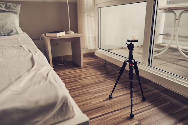 Room with unmade bed, book on the bedside table, light coming in through large windows with open curtains, tripod on wooden floor