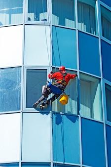 헬멧을 쓴 로프 접근 기술자는 고층 건물의 창문을 외부에서 세척한다
