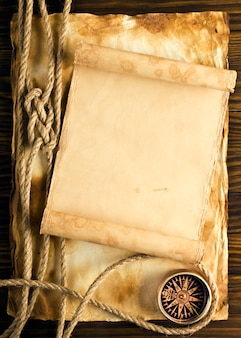 Rope and compass on the old paper surface
