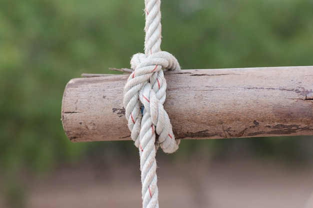 A rope is tied in a knot around a fence post, rope tied knot wood pole