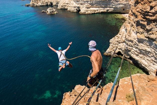 Веревка прыгает со скалы с веревкой в воде. океан. море. гора.