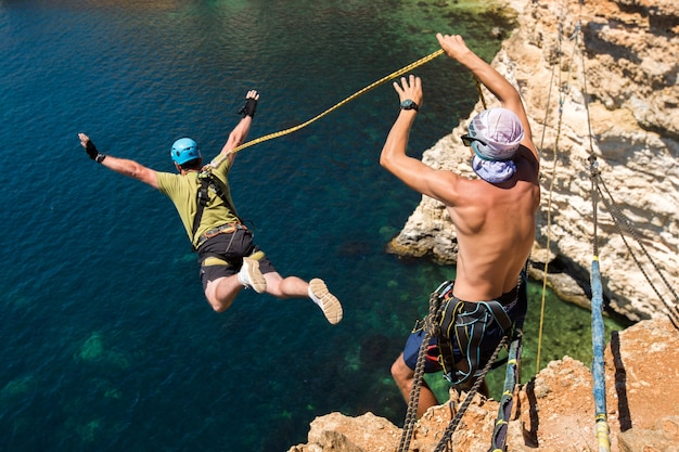 Rope jumping off a cliff with a rope in the water
