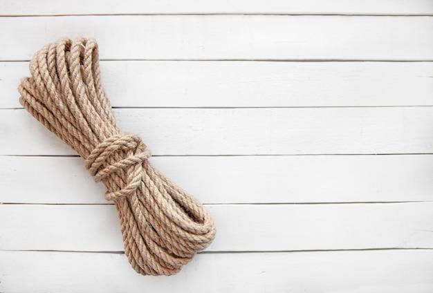 白い木製の背景に天然ジュートで作られたロープ。天然素材で作られた製品。
