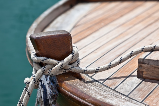 Веревка на деревянной палубе лодки. горизонтальный снимок с копией пространства