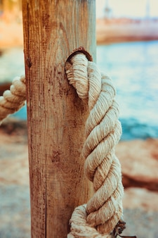 Rope railing of beach walkway, old wooden pole, blue sea sand in the background