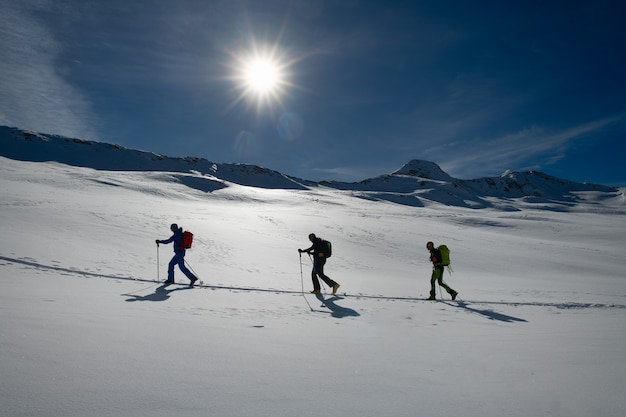 Rope of three ski mountaineers on a climbing track