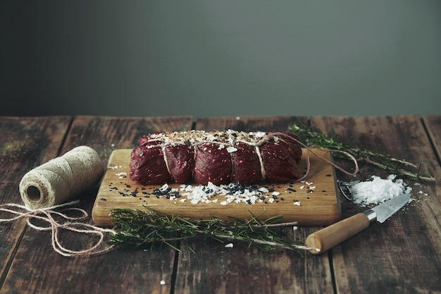 Rope tied salted peppered piece of meat ready to smoke on wooden table between herbs and spices on wooden