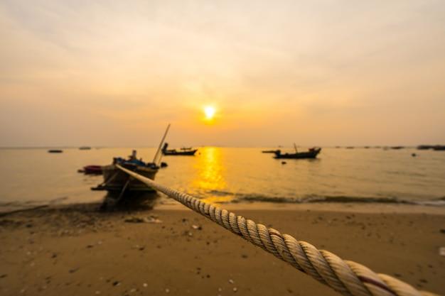 日没のビーチでロープを縛られて小さな漁船