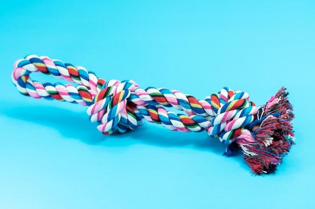 Веревочная игрушка для собаки или кота на синем фоне
