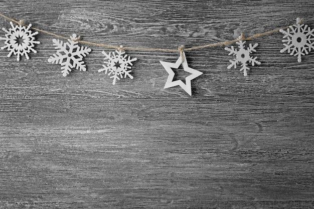 灰色の木製の背景に雪と星とロープ