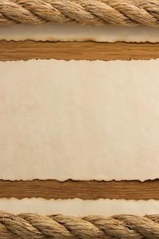 木製の背景でロープと古いヴィンテージ古代紙