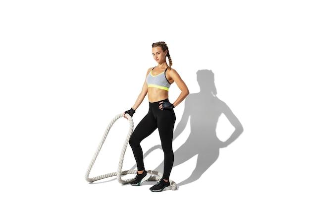 ロープ。白い壁、影の肖像画で練習している美しい若い女性アスリート。動きとアクションのスポーティーフィットモデル。ボディービル、健康的なライフスタイル、スタイルのコンセプト。
