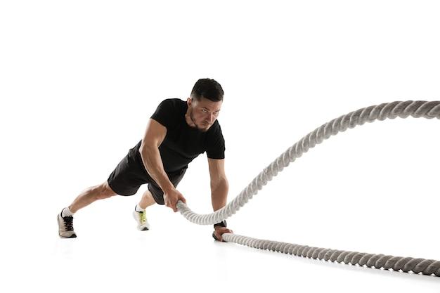 ロープ。白いスタジオでの白人プロスポーツマンのトレーニング。