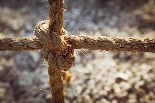 抽象的な背景が灰色の結び目で結ばれたロープ