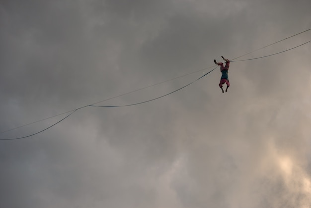 A ropewalker girl hangs upside down on the highline against the background of a dramatic sky