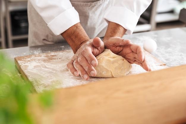 빵집이나 부엌에서 테이블에 생과자 용 반죽을 혼합하는 남성 손의 сropped 이미지