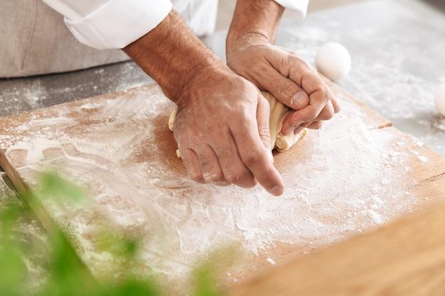 빵집이나 부엌에서 테이블에 생과자 용 반죽을 혼합하는 남성 손의 сropped 사진