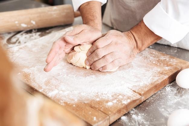 빵집이나 부엌에서 테이블에 생과자 용 반죽을 혼합하는 남성 손의 сropped 초상화