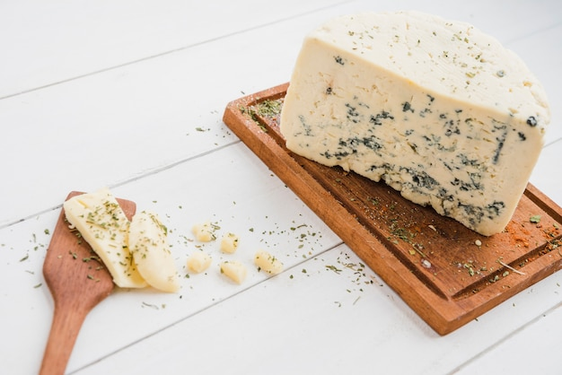 Roquefort cheese on wooden board with spatula on white table