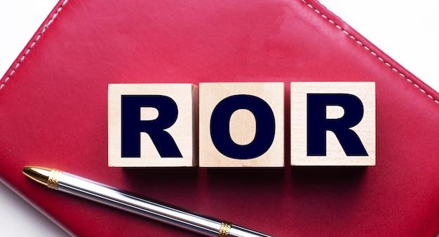 Ror состоит из деревянных кубиков, которые стоят на бордовом блокноте рядом с ручкой. бизнес-концепция