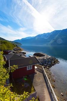 Rorbuer-遠くの湖畔と山々に立つ伝統的なノルウェーの赤い木造家屋、ノルウェー