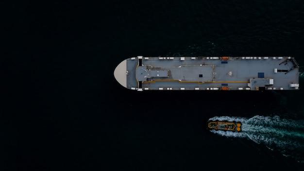 어두운 바다 공중 탑 뷰 운송 국제 개념에서 항해하는 로로 선박과 예인선