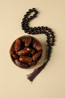 Rosary and bowl with dates on beige surface