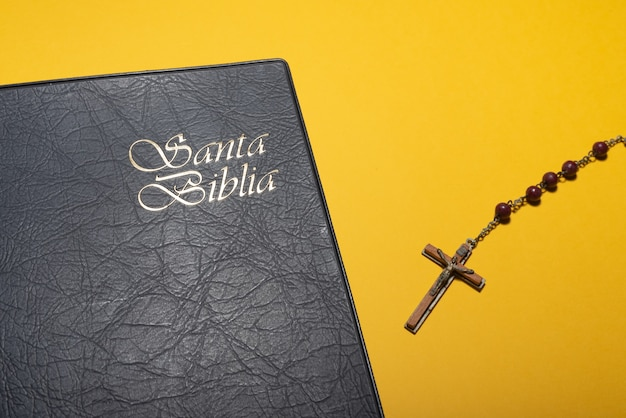 Rosary cross and santa biblia or holy bible on yellow