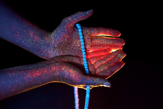 손에 묵주,기도. 손바닥을 통해 자외선, 신과 종교, 구슬로 빛. 손가락을 통한 신성한 빛