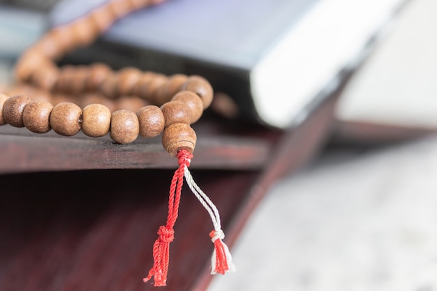 Rosary with red and white rope on wooden and quran for prayer bead