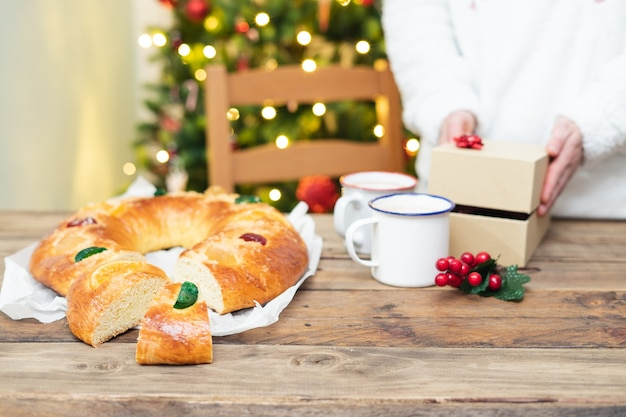Roscã³n de reyes (typical spanish sweet) cut, on a wooden table and christmas tree with lights in the background. christmas sweets and dessert.