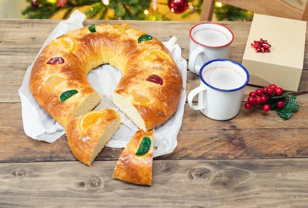 Roscon de reyesクリスマスデザート、クリスマスの装飾が施された木製のテーブルにカット。スペースをコピーします。