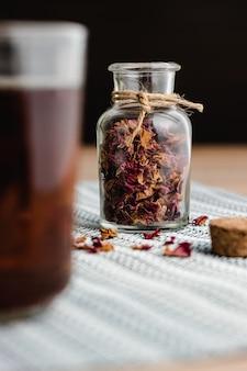 Роза и травяной чай в маленькой стеклянной бутылке