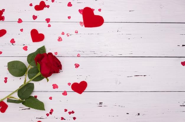 白い木製の背景、上面図にバラと赤のハート。コピースペース、バレンタインデーのコンセプト。