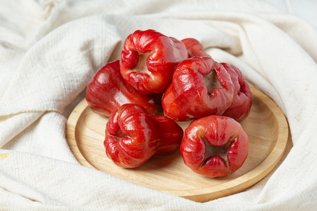 Rose apple on white wooden surface