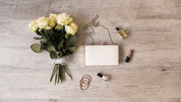 Rose bouquet; clutch; perfume; lipstick; nail varnish and hairbands on wooden background