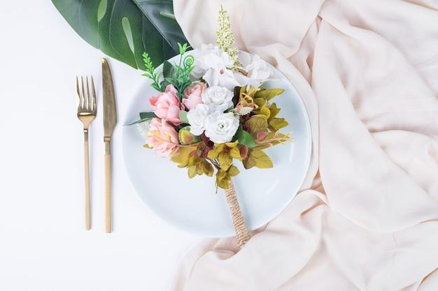 Букет роз, столовые приборы и тарелка на белой поверхности.