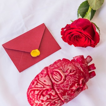 Роза ветка с конвертом на столе