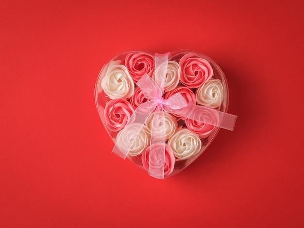 리본으로 묶인 하트 모양의 선물 상자에 장미 꽃 봉오리. 사랑의 개념.